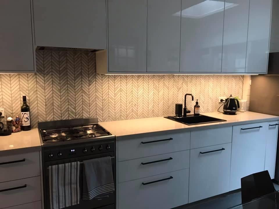 kitchen with big handles and herringbone splashback